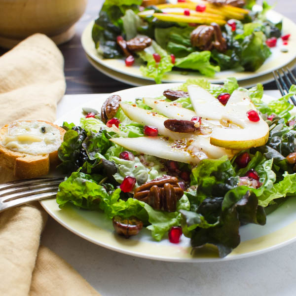 Pear Pomegranate Salad with Maple Dijon Dressing on plates.