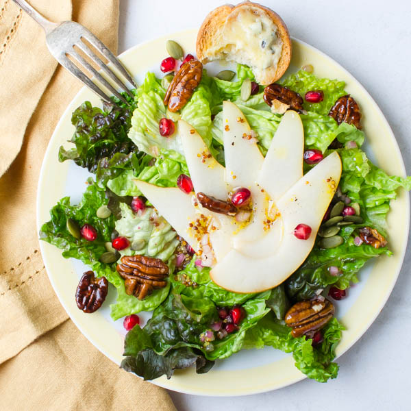 Pear Pomegranate Salad with Maple Dijon Dressing with fork and napkin