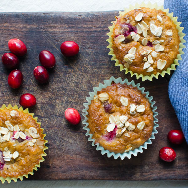 orange muffin recipe with fresh cranberries on a board.