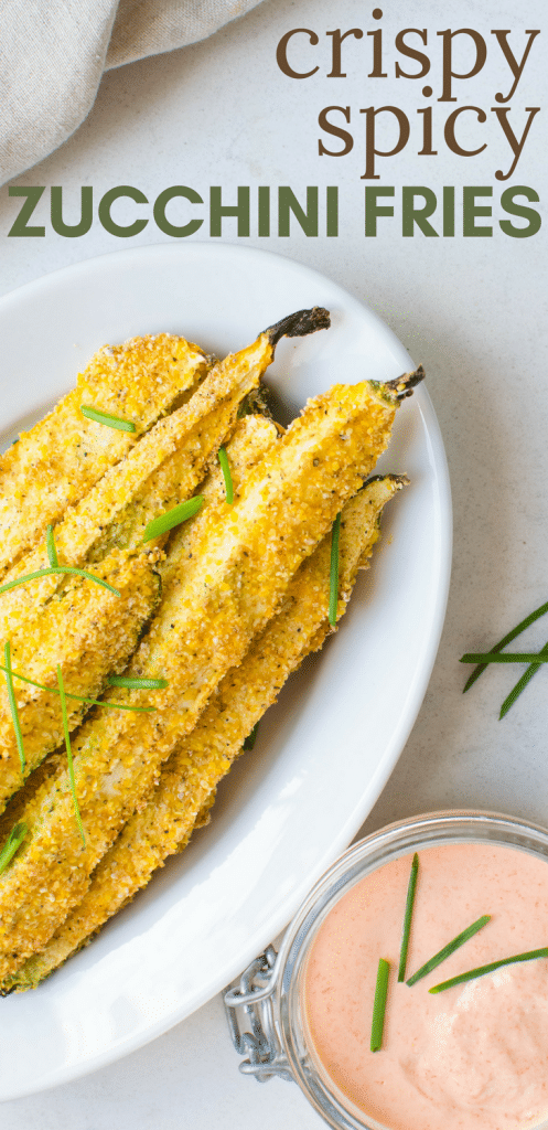 This healthier oven-baked zucchini recipe is quick and easy to make. Crispy Spicy Zucchini Fries are a delicious snack, appetizer or side dish. A gluten-free cornmeal crust and sweet pepper aioli for dipping will have even the pickiest eaters devouring their vegetables. #zucchini #squash #appetizer #snacks #sidedish #ovenfries #healthierfries #fries #glutenfree #cornmeal #eggwhites #vegetariansnacks #vegetarianappetizer #glutenfreesuperbowlsnacks #pickyeaters #easybakedfries #bakedfriesrecipe