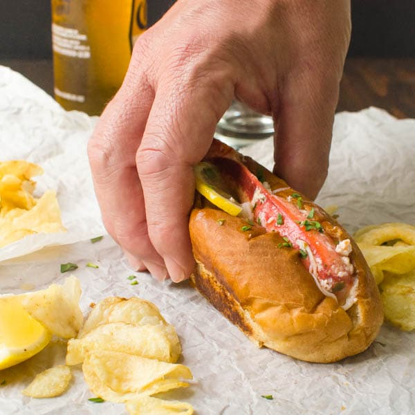 hand holding a Warm Lemon Butter Lobster Roll