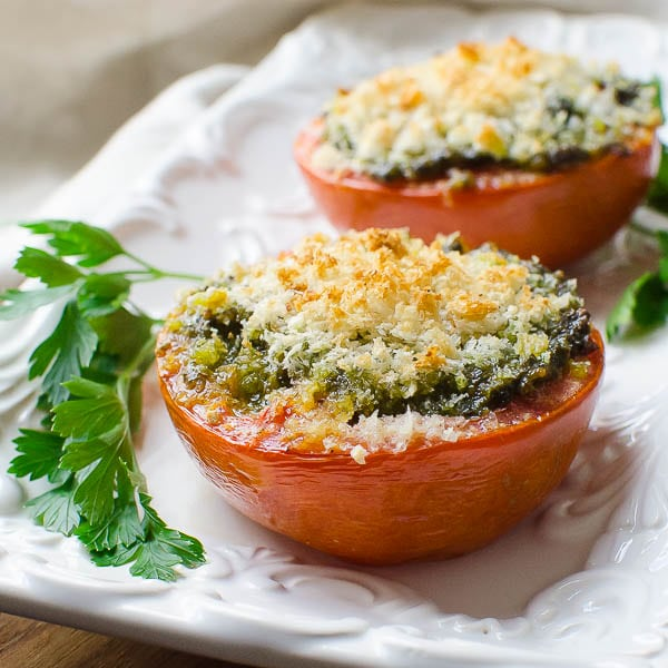 roasted tomatoes with pesto and toasted breadcrumbs on a platter.
