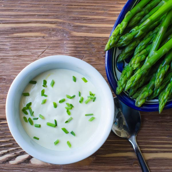 asparagus on a plate with dijon sauce in a ramekin