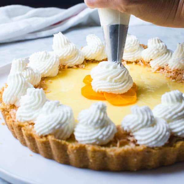 piping whipped cream into the center of the calamondin pie.