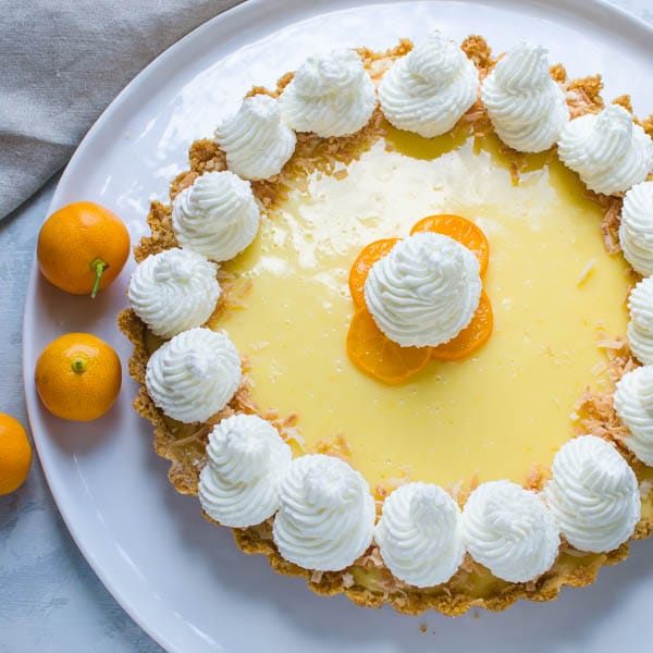 overhead picture of calamondin pie with two oranges on the side.