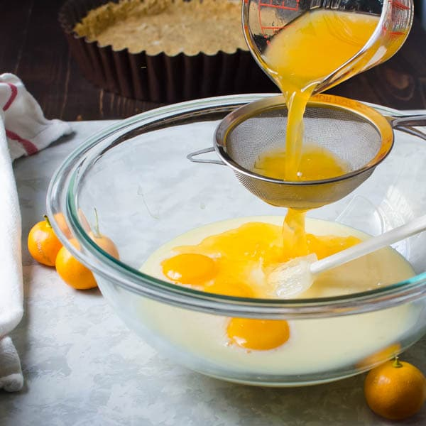 straining calamondin juice into a bowl with egg yolks and sweetened condensed milk.