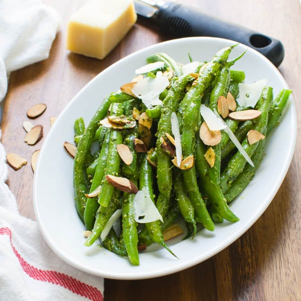 Spring Pesto Green Beans on a platter with cheese and almonds.