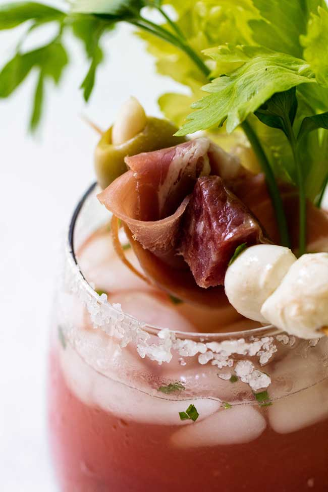 Bloody Mary Italian Style with a closeup of the garnish, salami, prosciutto and cheese with celery.
