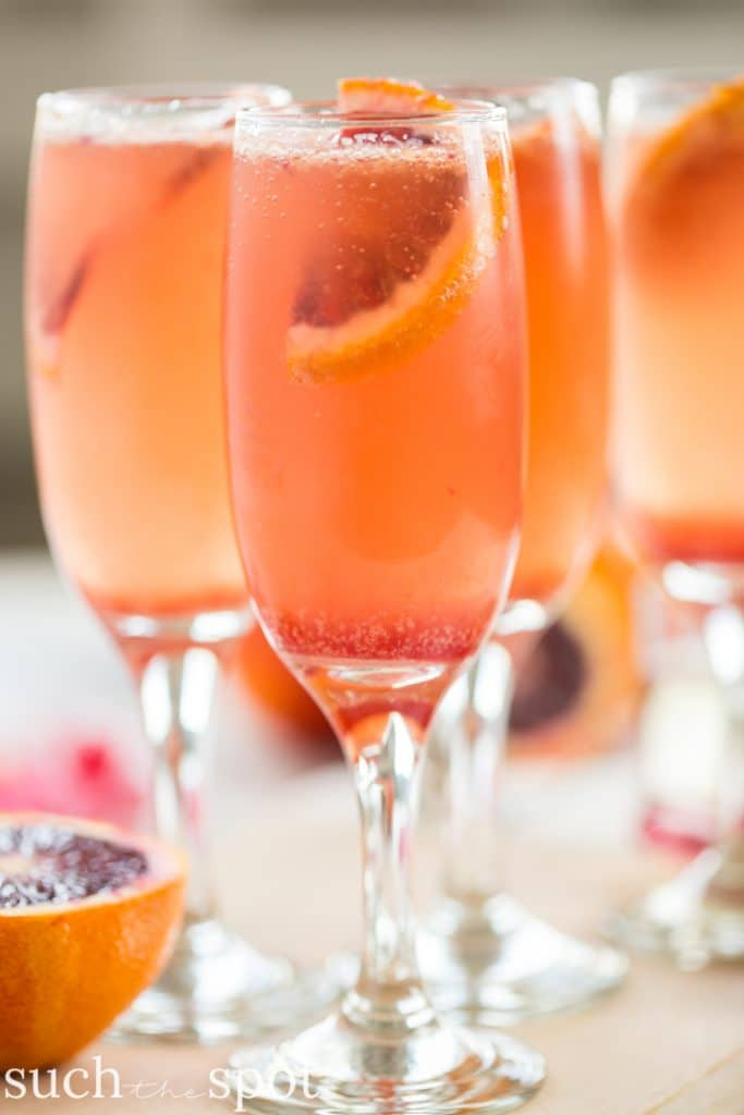 elderflower blood orange mimosas in champagne flutes with blood orange garnish.