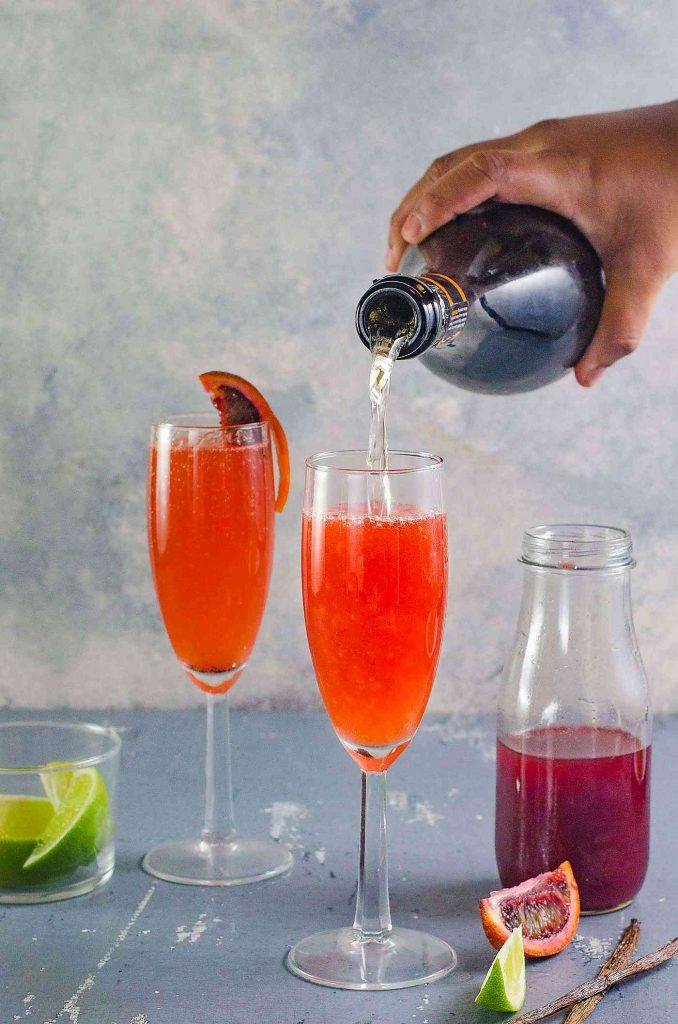 pouring champagne into the blood orange mimosa
