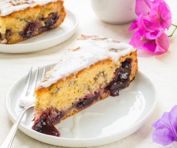 Glazed Cherry Almond Coffee Cake slice on a plate with fork.