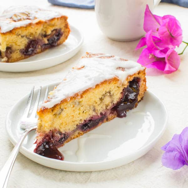 Glazed Cherry Almond Coffee Cake slice on a plate with fork.