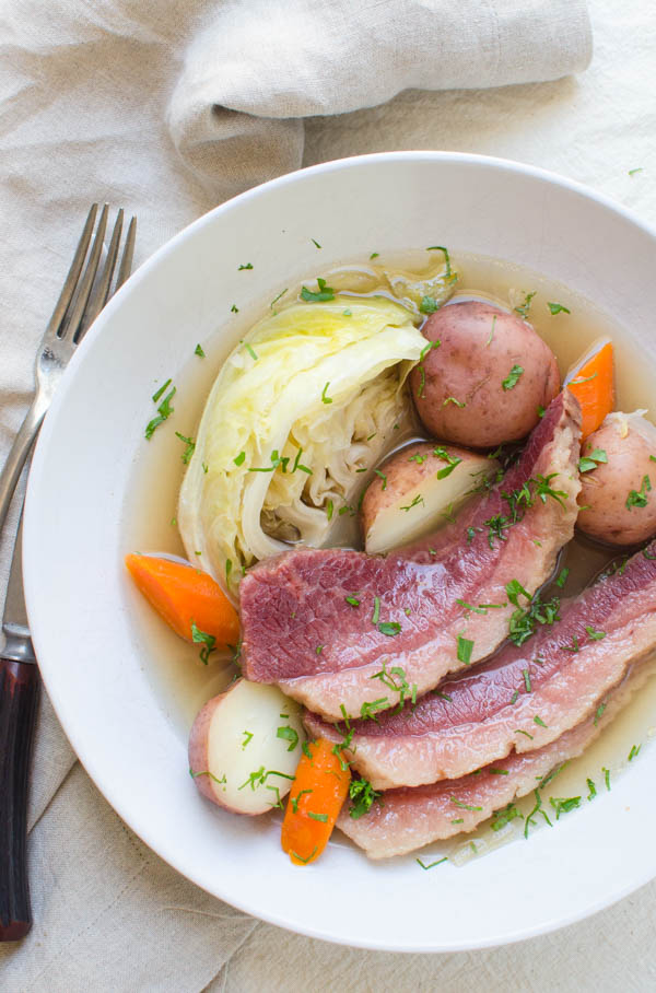 Serving corned beef and cabbage in a bowl with potatoes and carrots.