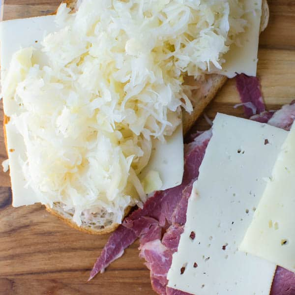 photo of the reuben sandwich being assembled with sauerkraut, swiss cheese and corned beef.