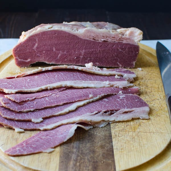 corned beef being sliced on a cutting board.
