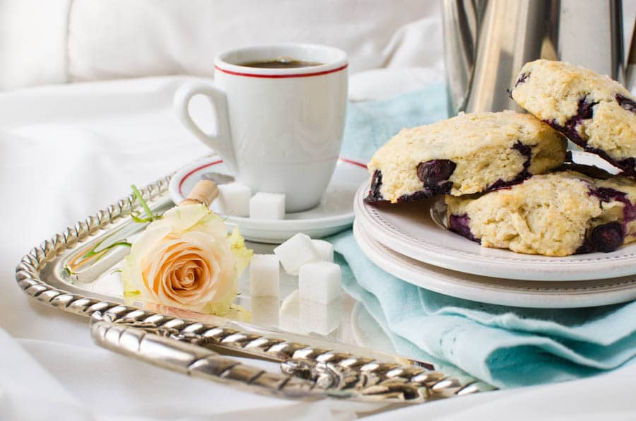A silver tray with blueberry cream cheese scones, coffee and sugar cubes with a single rose - served breakfast in bed style.