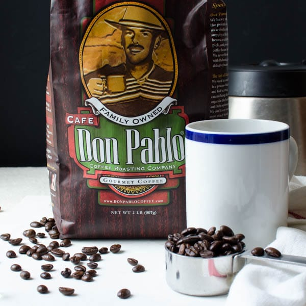 A bag of Don Pablo coffee and large scoop of whole coffee beans with a coffee cup.