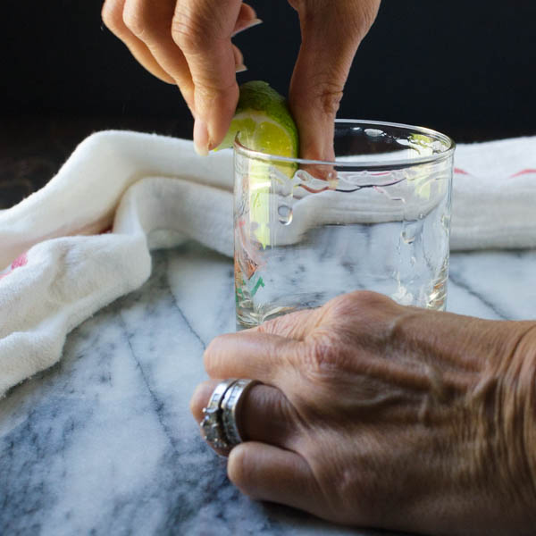 photo of a hand holding a lime and rimming a glass with the lime juice.
