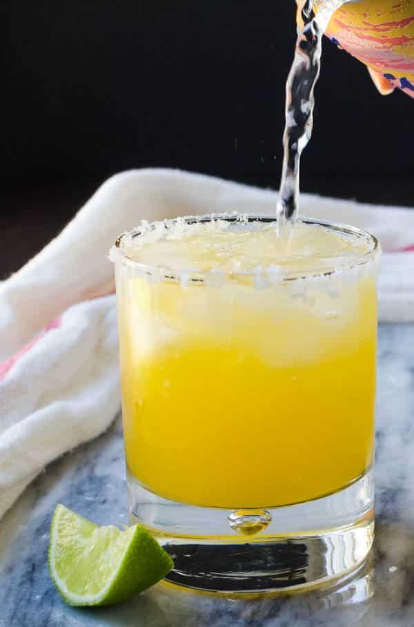 adding sparkling water to the cara cara margarita.