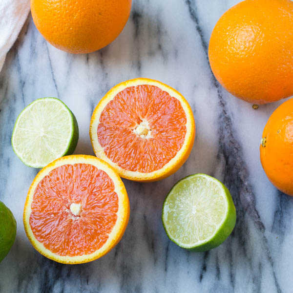 sliced cara cara oranges and limes on a marble background