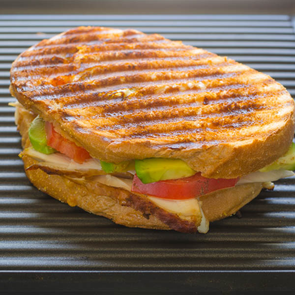 California Smoked Chicken Panini on press with fillings showing.