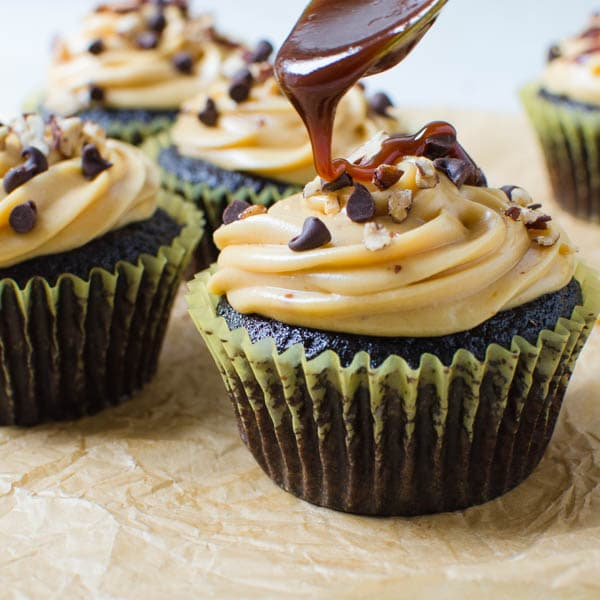 Spooning caramel sauce over Small Batch Turtle Cupcakes