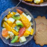 Rum Spiked Tropical Fruit Salad in a bowl with spoon.