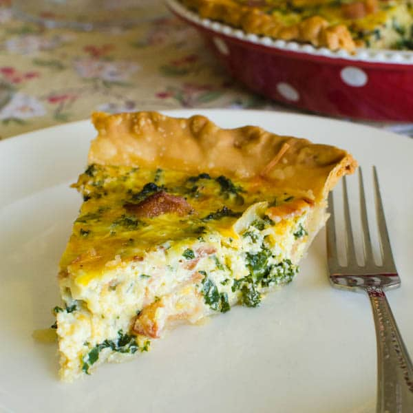 A slice of Bacon Cheddar Kale Quiche on a plate with a fork.