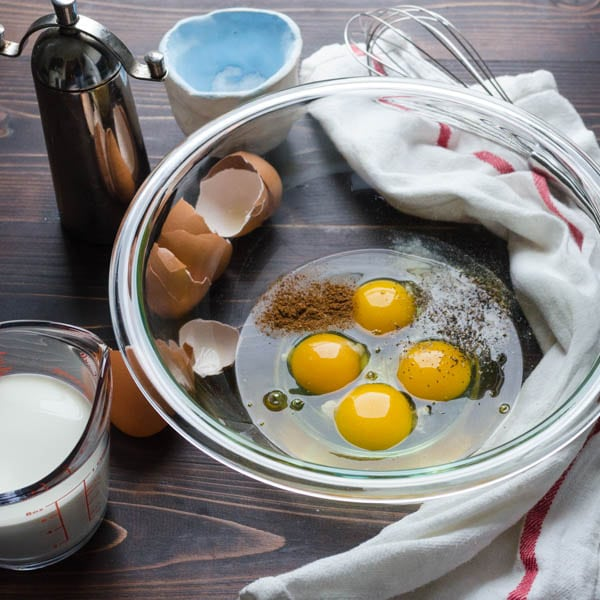 A glass bowl with 4 eggs, salt, nutmeg and pepper. A cup of cream on the side.
