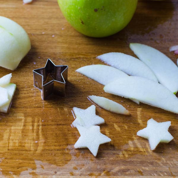 cutting apple slices with star shaped cutter.