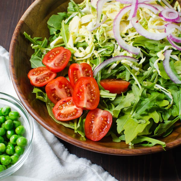 adding tomatoes, onions and peas to the salad.
