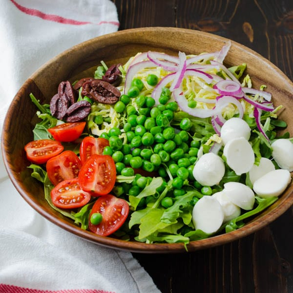 adding olives and cheese to the salad.