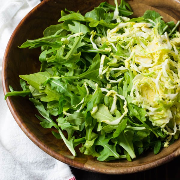 arugula and shaved brussels sprouts in a bowl.