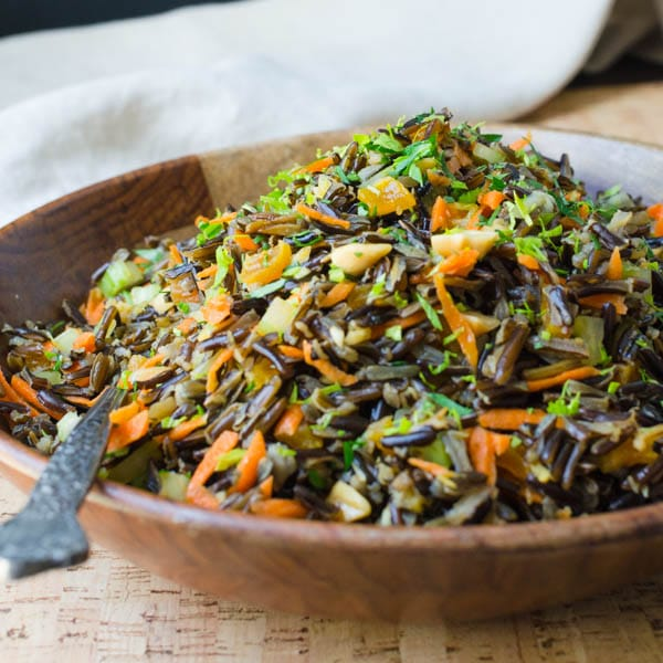 Asian Wild Rice Salad with Ginger Soy Dressing in a bowl with serving spoon.