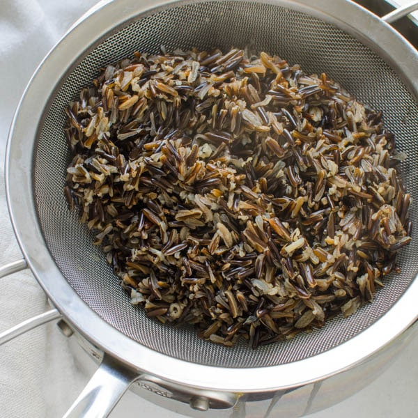 cooked wild rice in a strainer.