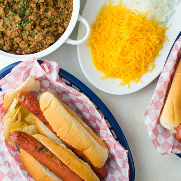 hot dogs in a bun with condiments all around.