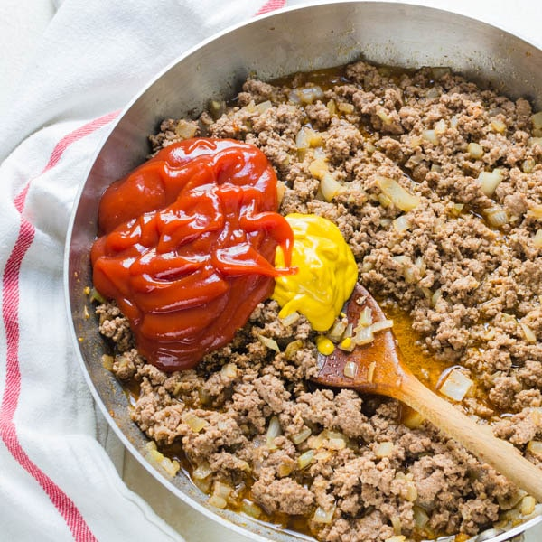 adding ketchup, mustard, vinegar and worcestershire sauce to the ground beef.