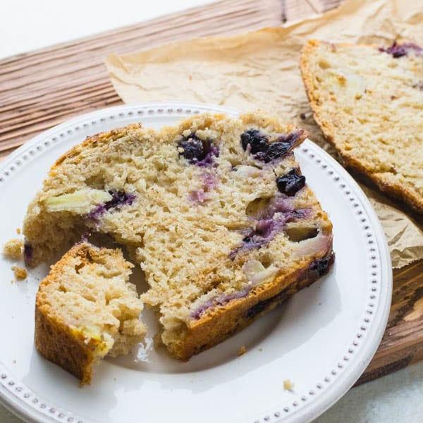Best Blueberry Banana Bread recipe sliced on a plate.