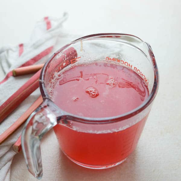 rhubarb ginger simple syrup in a measuring cup.