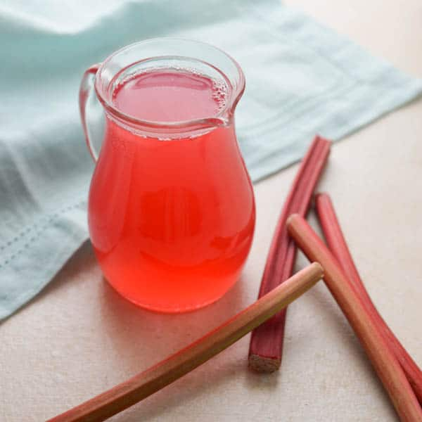 rhubarb ginger simple syrup in a small pitcher with fresh rhubarb beside.