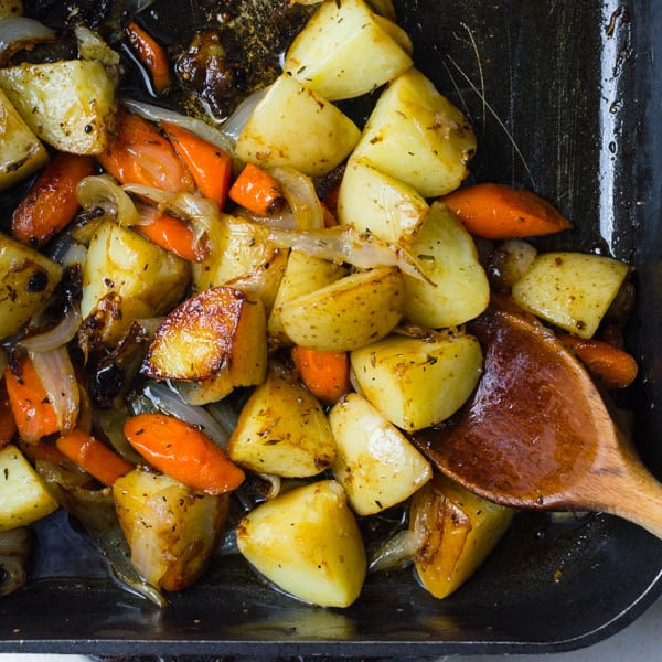 roasted root vegetables in a roasting pan with wooden spoon.