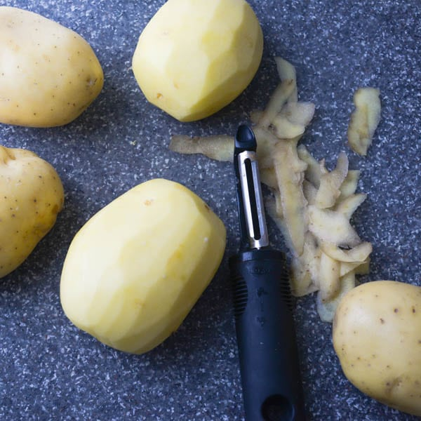 peeling potatoes for Simple Scalloped Potatoes.