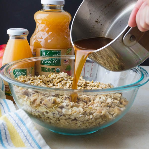 pouring the apple juice mixture into the oat mixture.