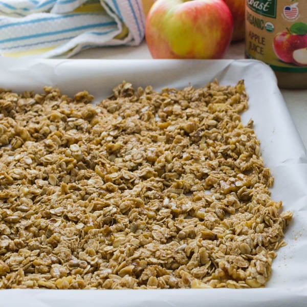 spreading naturally sweetened crunchy granola on a baking sheet.