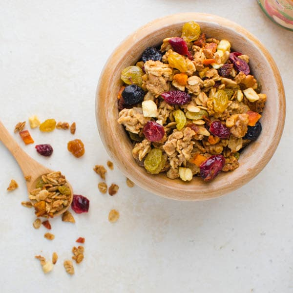 naturally sweetened crunchy granola with a wooden spoon.