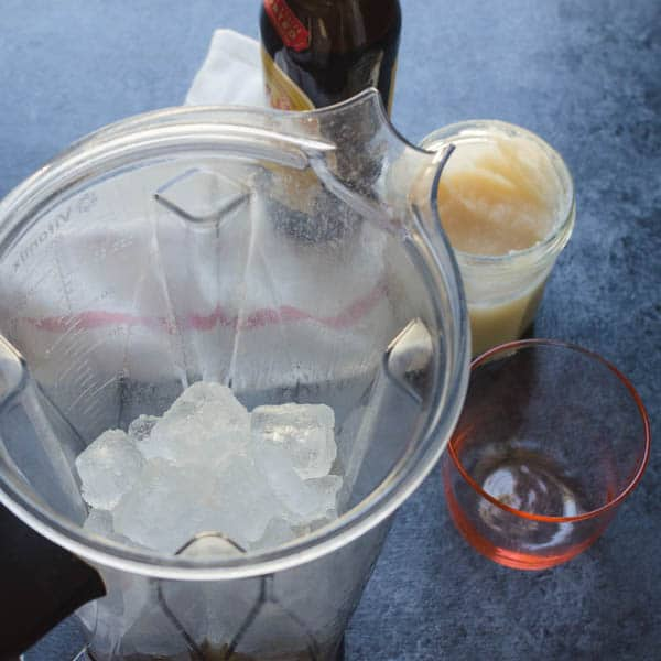 adding ice to the ingredients in the blender.