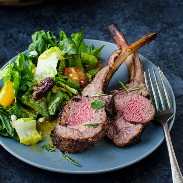 herb crusted rack of lamb, cut into chops on a plate.