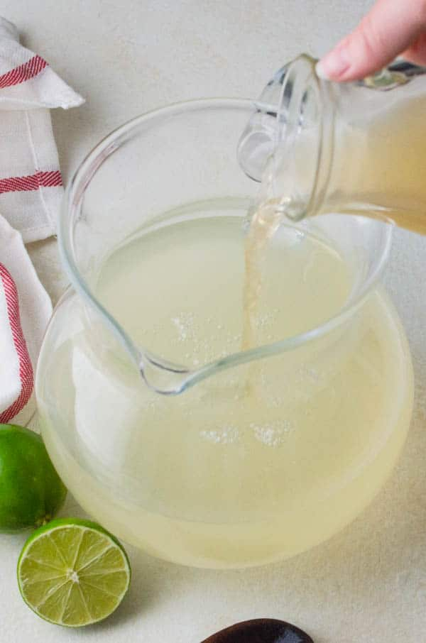 pouring guava syrup into limeade.