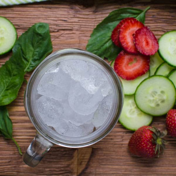 glass of ice and sliced cucumbers and strawberries.