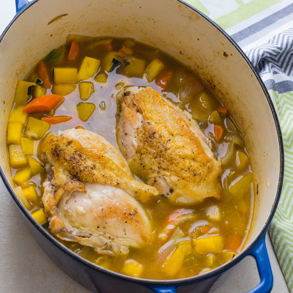 adding broth and seared chicken to the healthy chicken stew.